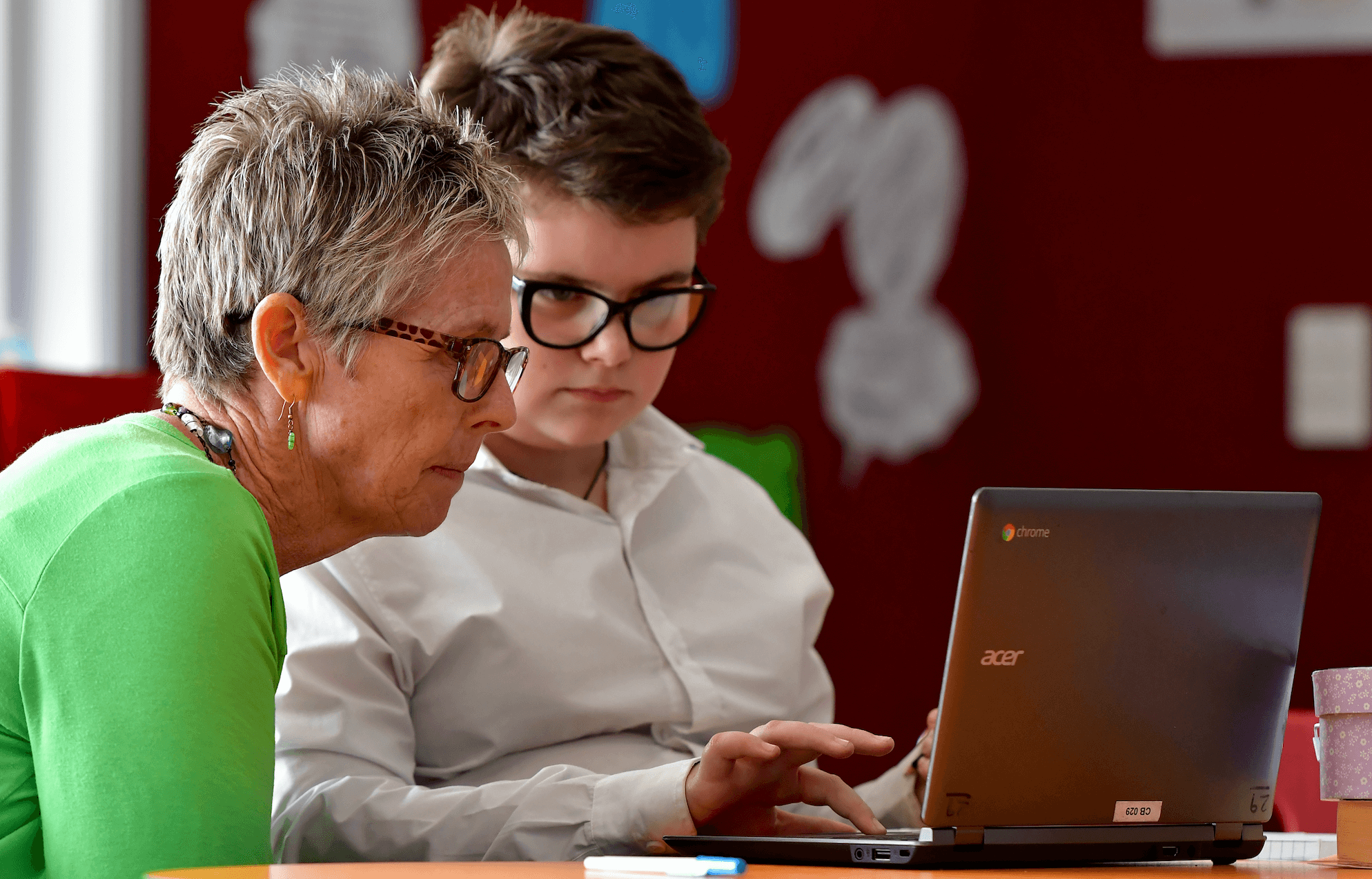 Male student and female teacher working together on laptop