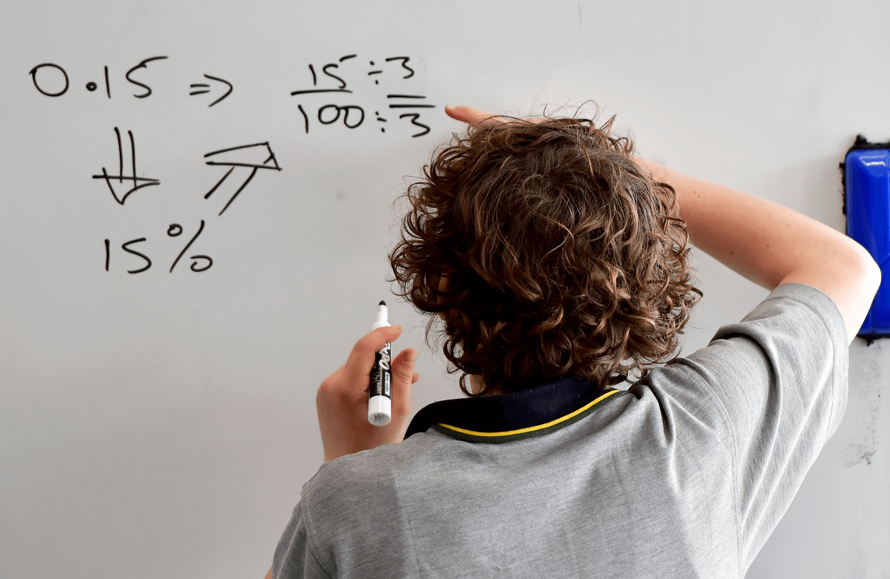 Male student writing on whiteboard