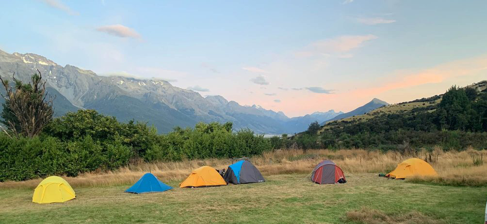 5 tents with mountains in the background